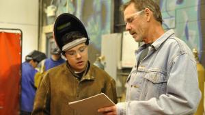 Greg Reiche works with Angelo Chavez in Jake Lovato's Santa Fe High School welding class.